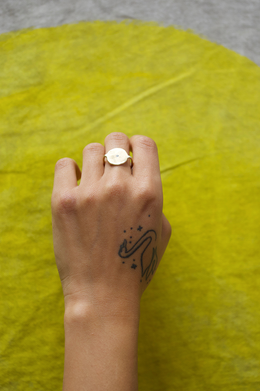 The  Hyalite Diamond  ring in 14k yellow gold in front of a hand painted sun on a linen throw (coming soon)