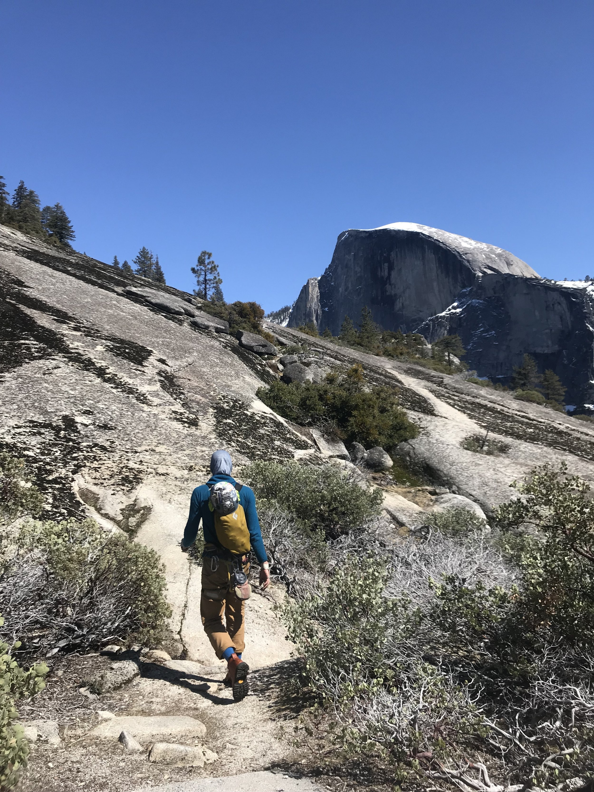 Cary walking off Royal Arches with Half Dome in the background.
