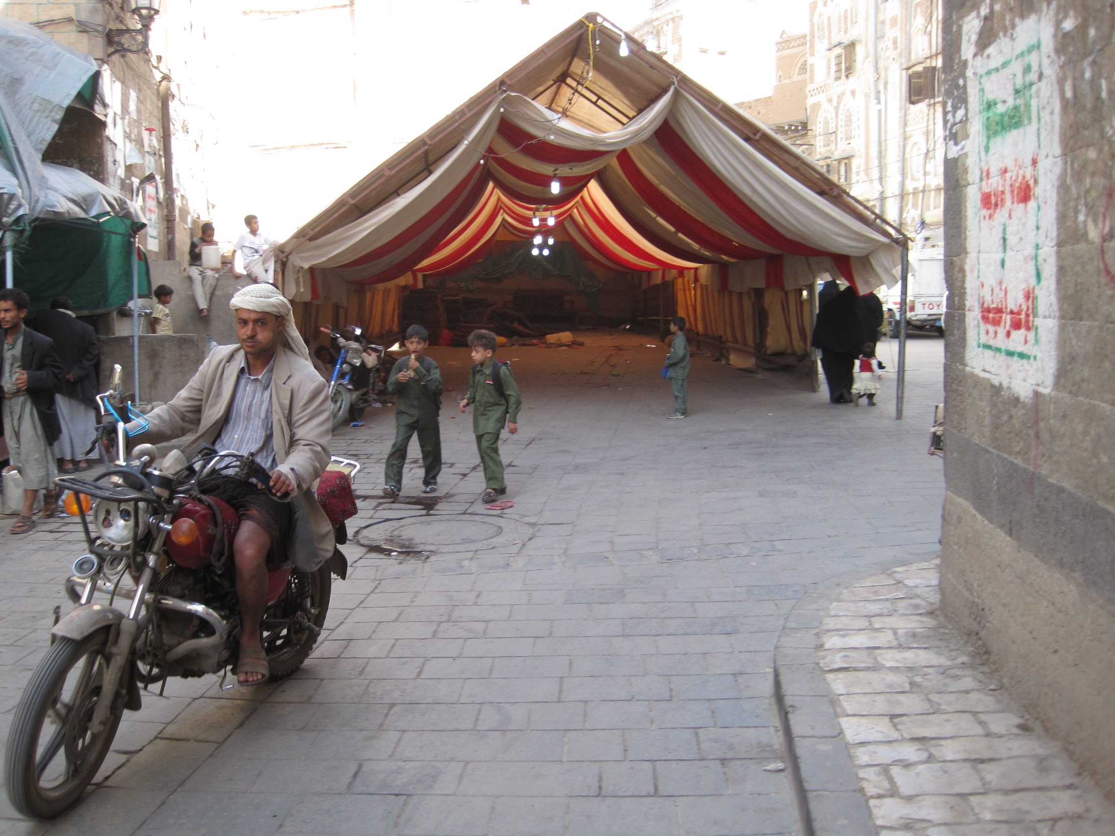 A man on a motorcyle in the Old City of Sana'a, behind him the tent for the wedding (which took place at night).