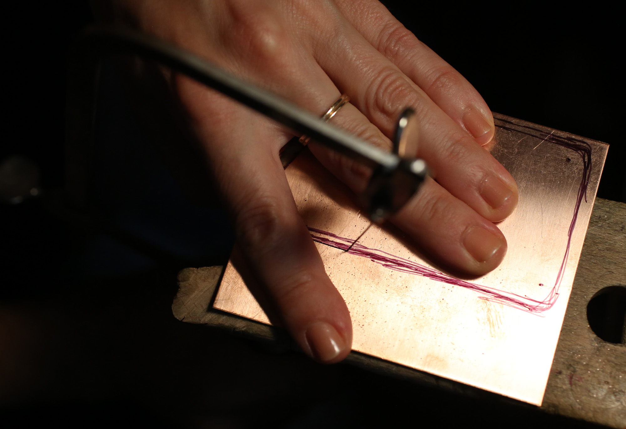 The beginning step of an enameled pendant- piercing copper sheet with a jeweler's saw.