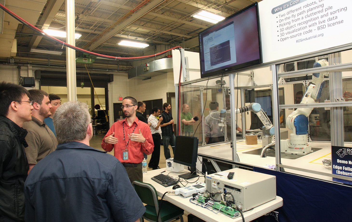 Shaun Edwards (red shirt, SwRI) in his element explaining how to configure MoveIt! to control the Motoman SIA20D (right robot).