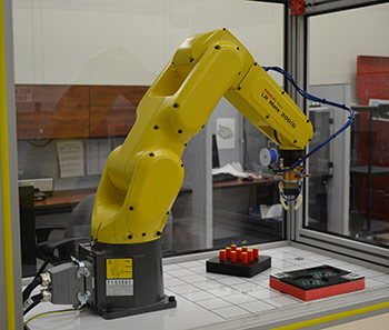 Robot challenged to demonstrate its dexterity on NIST test artifacts. The new ARIAC competition will focus on agility—how well robots can perform a diverse set of tasks and how quickly they can be re-tasked.Photo Credit: NIST/D. Russell