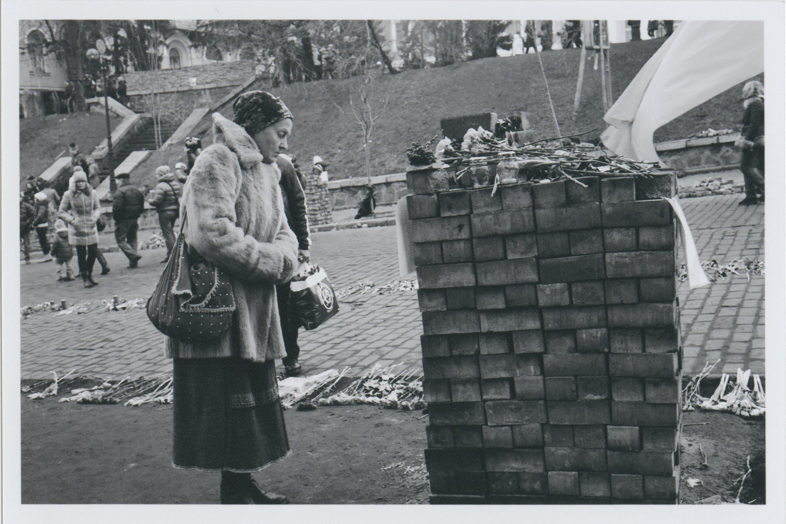 A woman standing next to a newly made brick wall, made from the stones in the street. Where there is dirt in this picture, there once was a beautiful stone road. Behind here, you can see a flower path. There was a flower road leading up the street where 76 people were killed by government snipper fire.    Photo: Michael Berlucchi