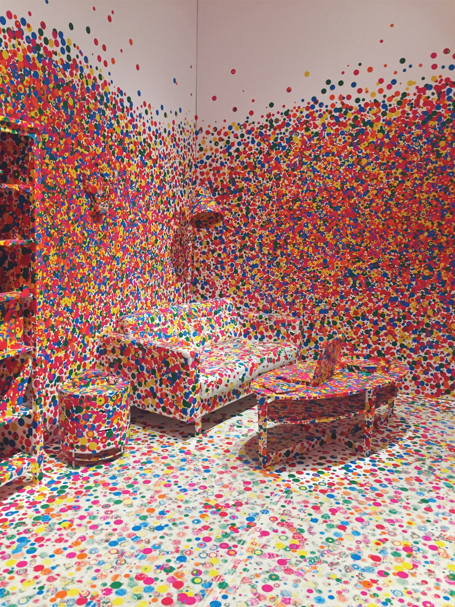 Yayoi Kusama, The Obliteration Room  (2002), is an all-white replica of a traditional domestic setting. Upon entering, visitors are invited to cover every surface of the furnished gallery with multi-coloured polka dot stickers, gradually obliterating the entire space in colour.