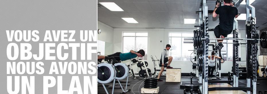 Démontrant la salle de musculation du gymnase, cette image permet d'observer l'importance de la combinaison des exercices de renforcements musculaires avec ceux de flexibilité, afin d'éviter blessures et inconfort. En gymnastique acrobatique, lors des stunts et des acrobatie, cela peut s'avérer crucial de maximiser ses gains en force et en stabilité articulaire à court, moyen et long terme.