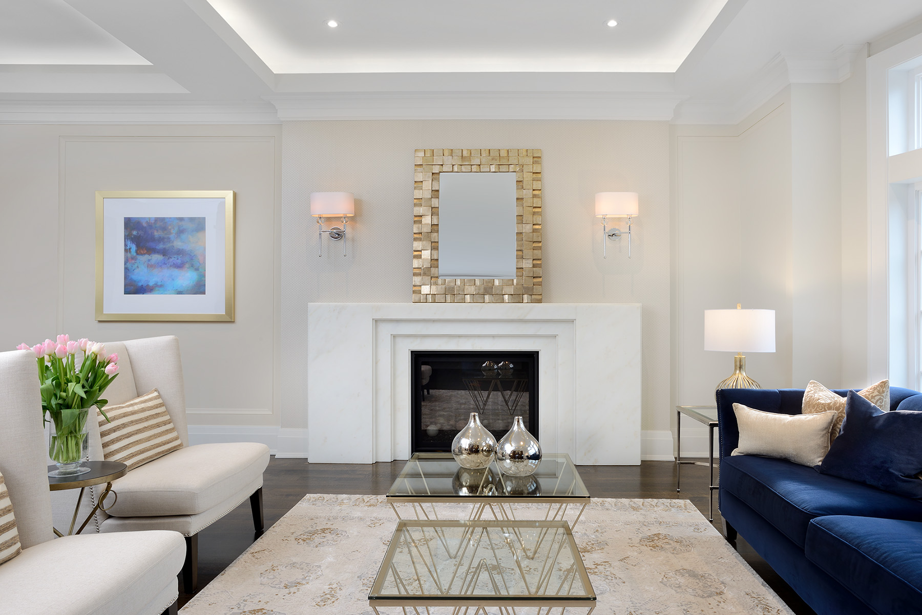 Transitional - The shape and squared off details of the marble fireplace are reflected in the ceiling which has led lighting as an added feature for ambiance.