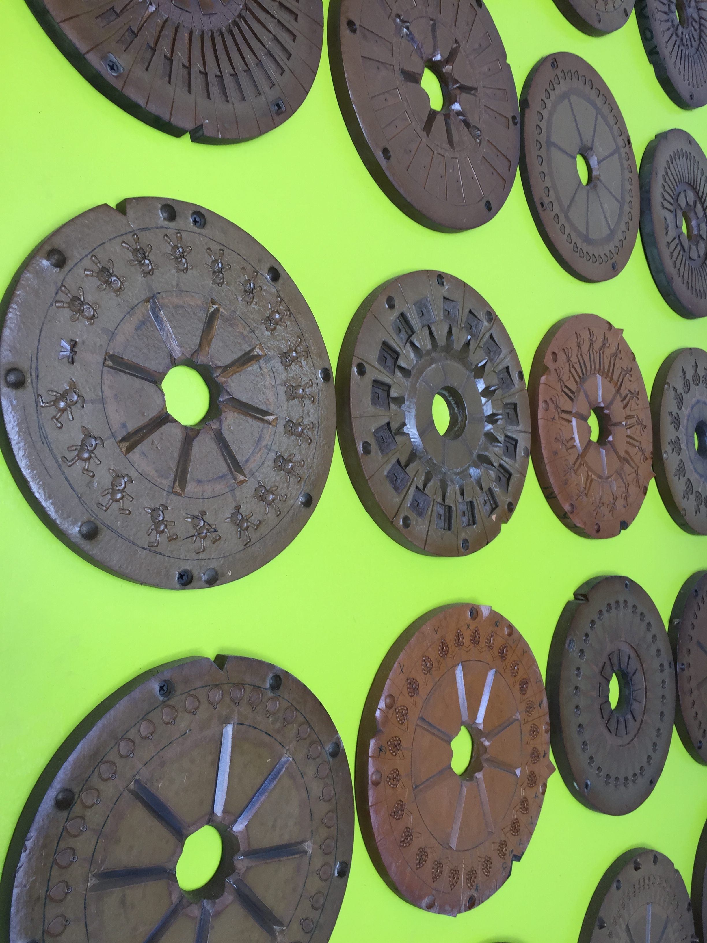 These are old jewelry molds Alison found in an old, Pawtucket mill. She collected them, each with different patterns, and cleaned them up. On top of a bright, lime green wooden screen, hanging on plumbing pipe frames, these serve to hide the outdoor fridge and pool equipment.