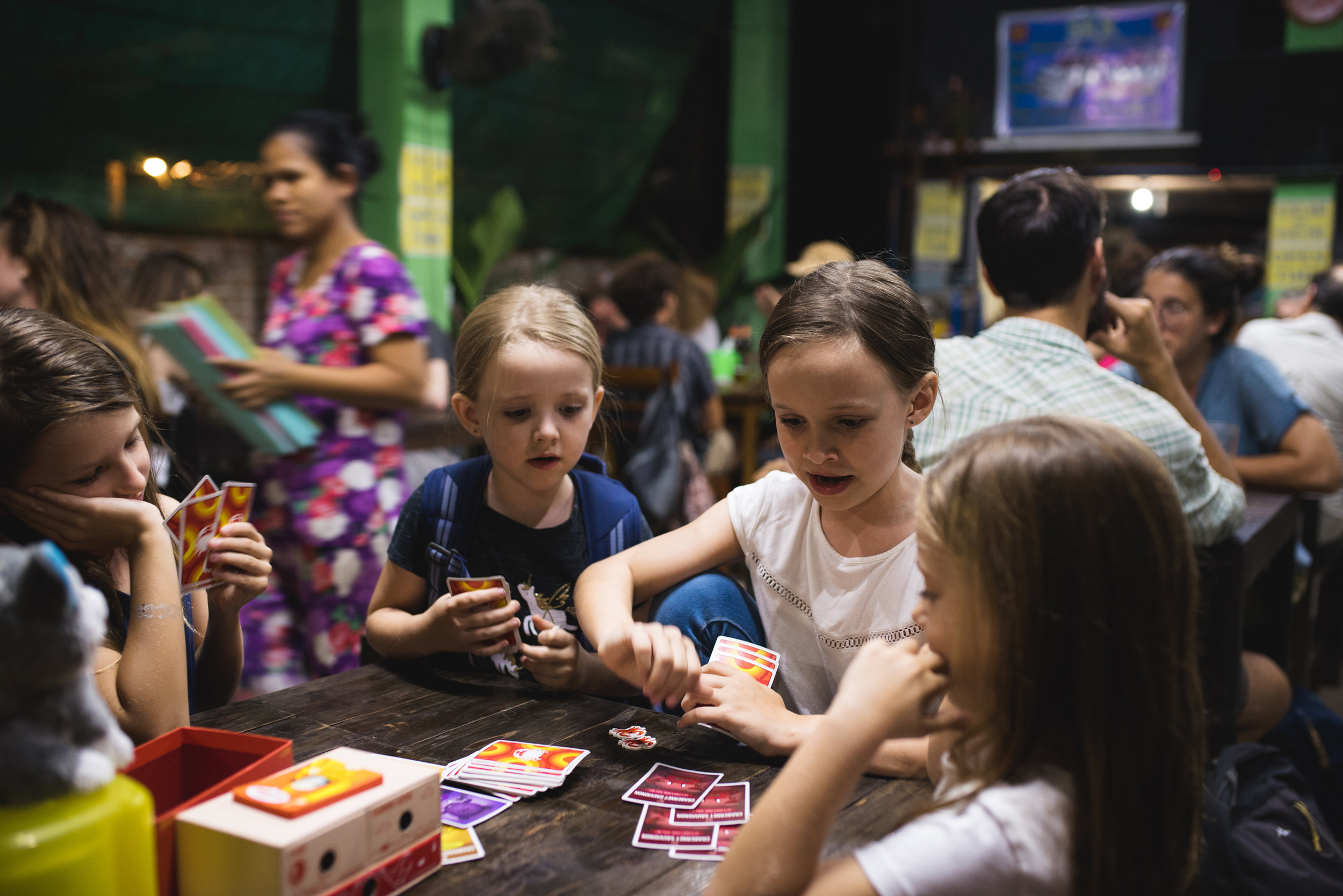 The kids playing cards at a local restaurant. (note the backpack!)
