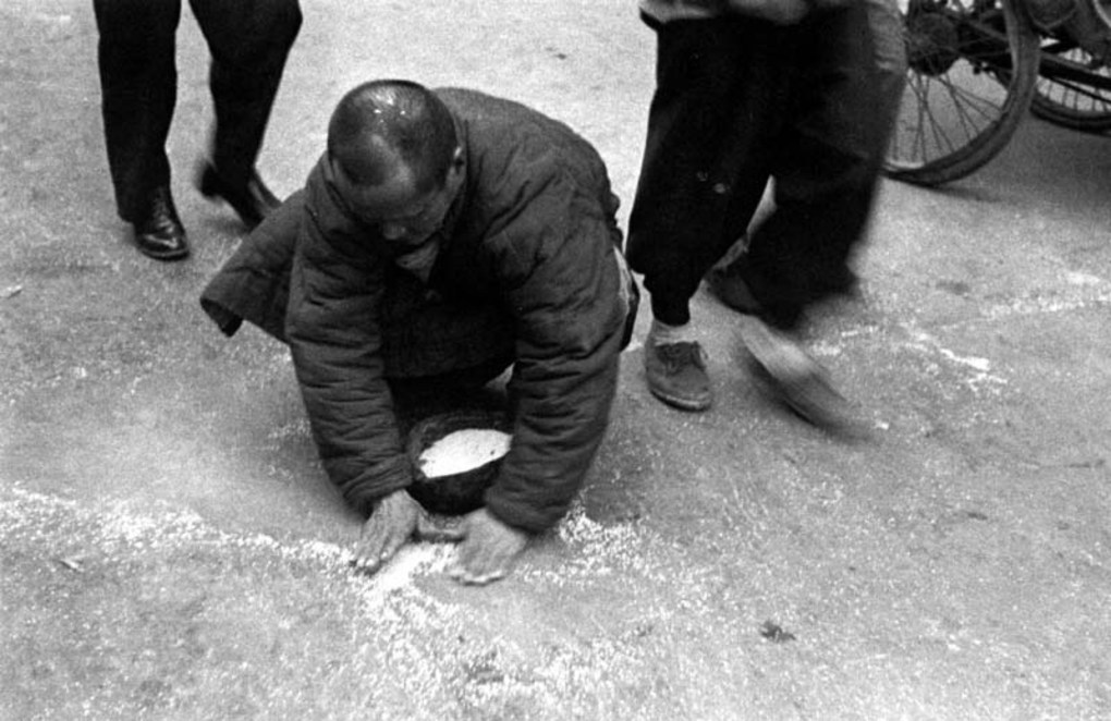A poor man picking up spilt rice in the street, 1949. Image courtesy of the Institut d'Asie Orientale and Virtual Shanghai