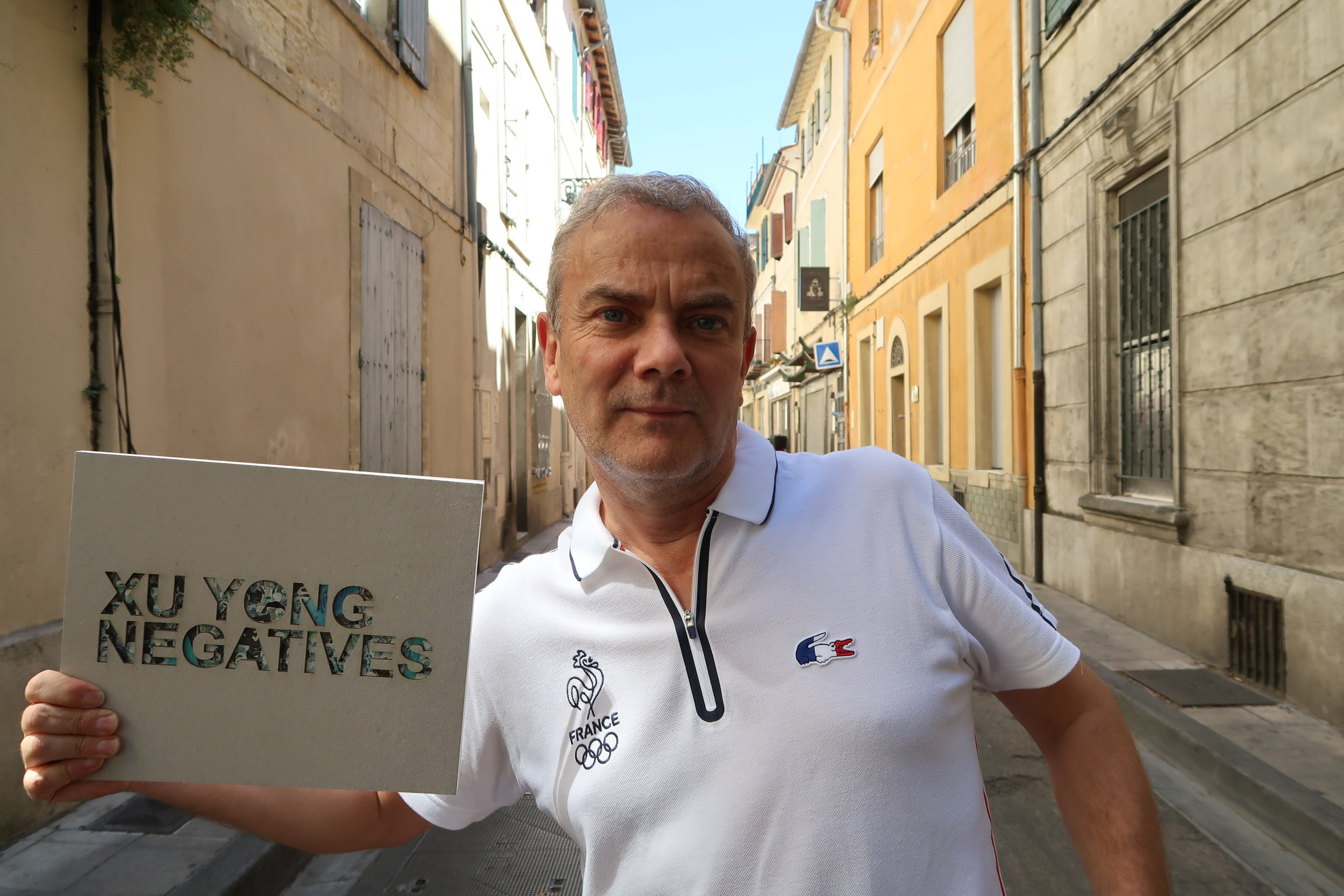 """Pierre Bessard holding his Xu Yong's """"Negatives"""" monograph published by his eponymous publishing house in 2017"""
