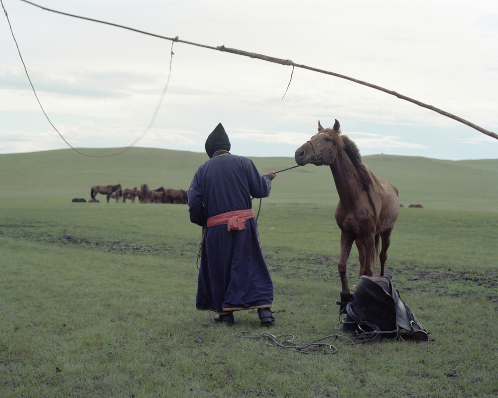 A Mongolian man is leading a horse,Inner Mongolia,2011-li-wei-photography-of-china.jpg