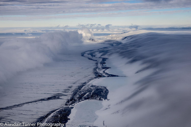Clouds fall over Minna Bluffs, Antarctica. Shot from a Twin Otter.