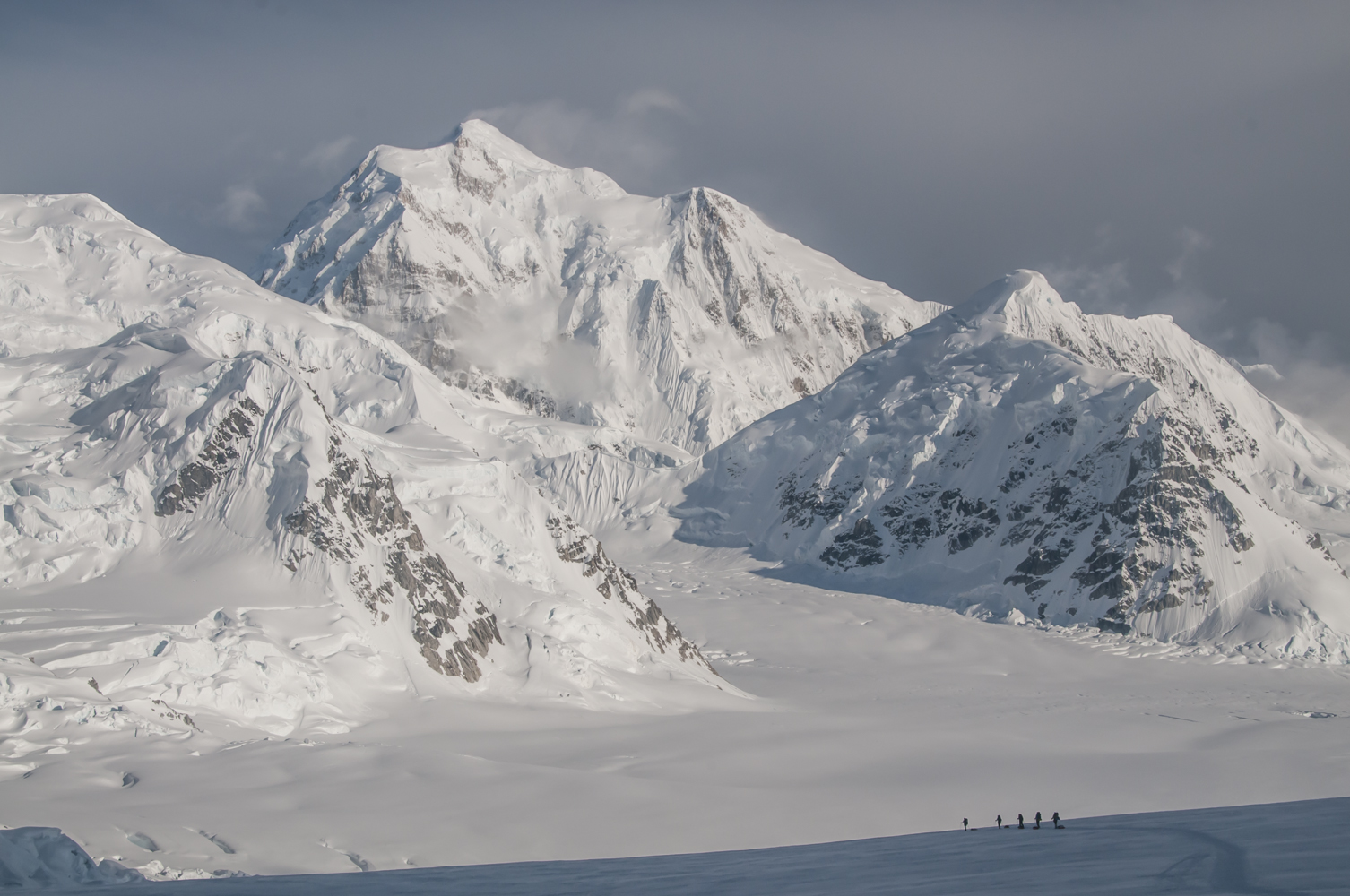 A rope team heads down Ski Hill on the Kahiltna Glacier, with Mount Hunter in the background.