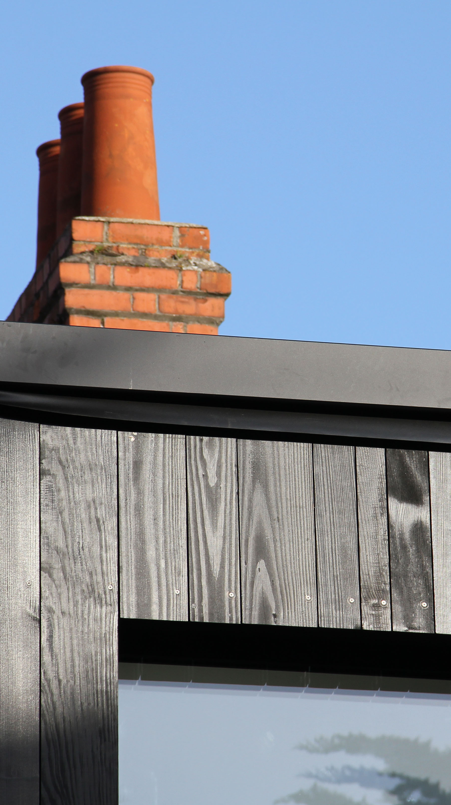 Black stained timber clad extension with old chimney in background