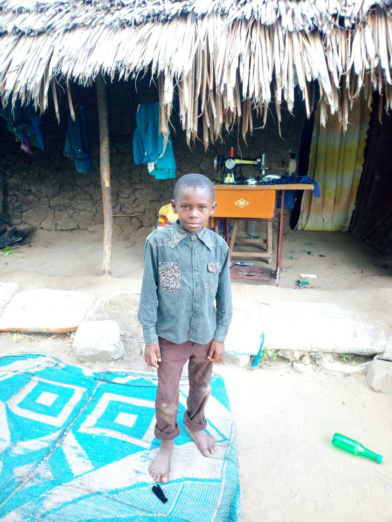 This is Noshadi in front of his home. The sewing machine is treadle powered by his mother, a tailor.