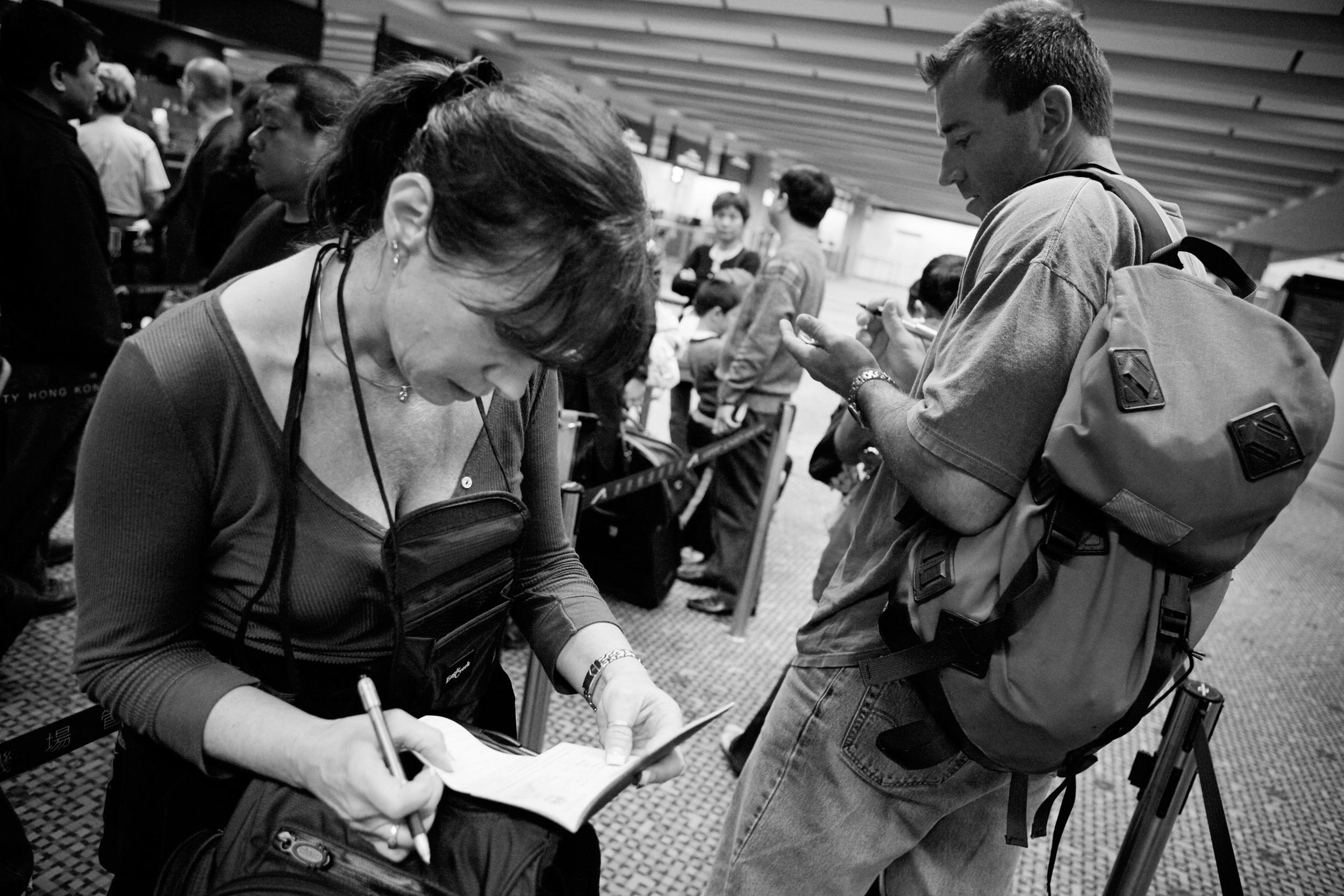 Karen and Bob check their passports after arriving in Hong Kong, China.
