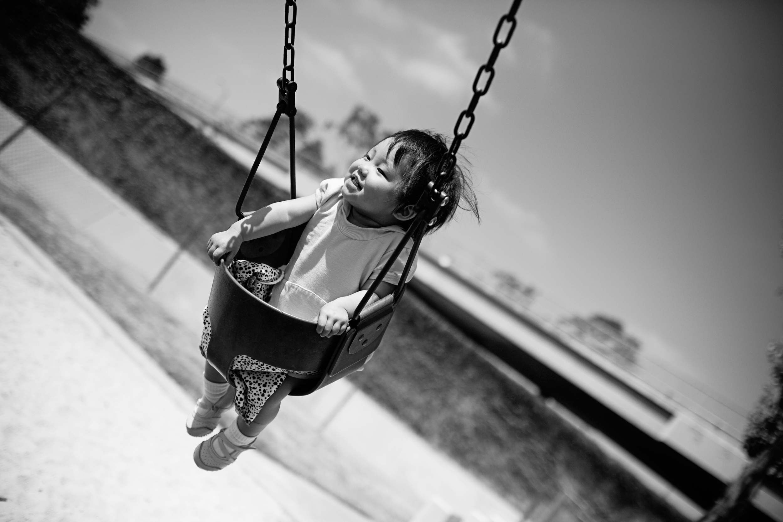 Kailee enjoys the swings at a playground.