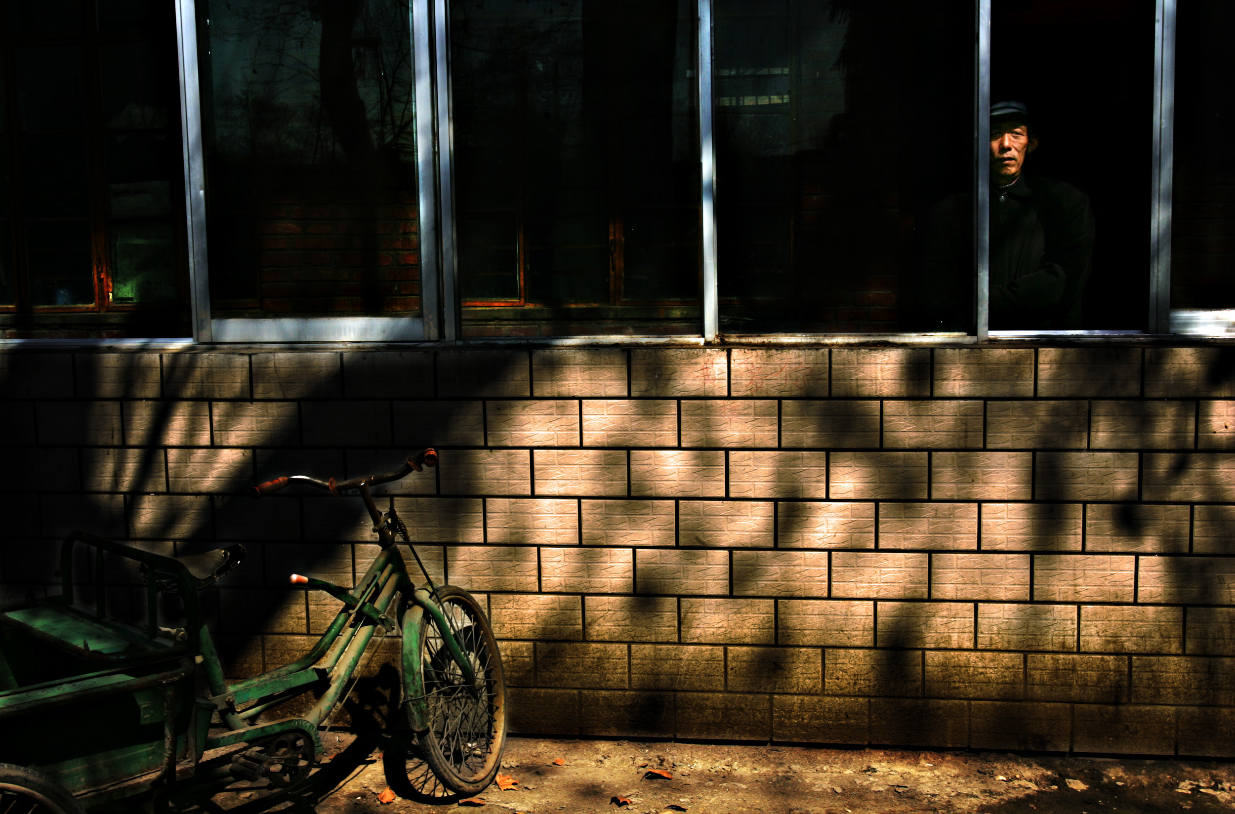 A patient gazes out the window in the cancer ward of Shenqiu County Hospital.