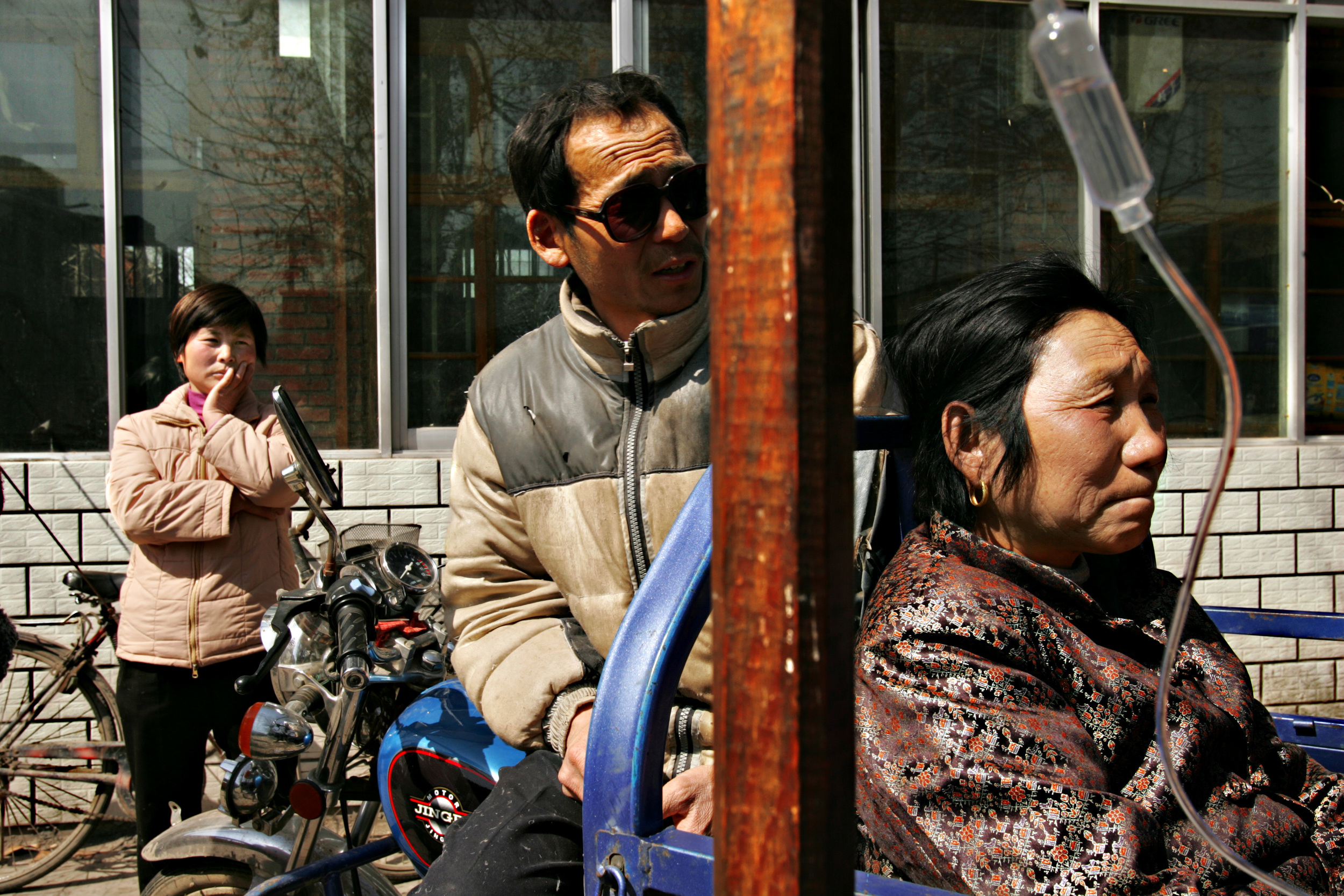 Jia Yumei, 55 (right) , from Sunying Village waits outside of the Cancer Ward of the Shenqiu County Hospital with her daughter and son in law. She has been driven to the hospital on the back of a motorcycle cart and is awaiting treatment for an undisclosed illness.