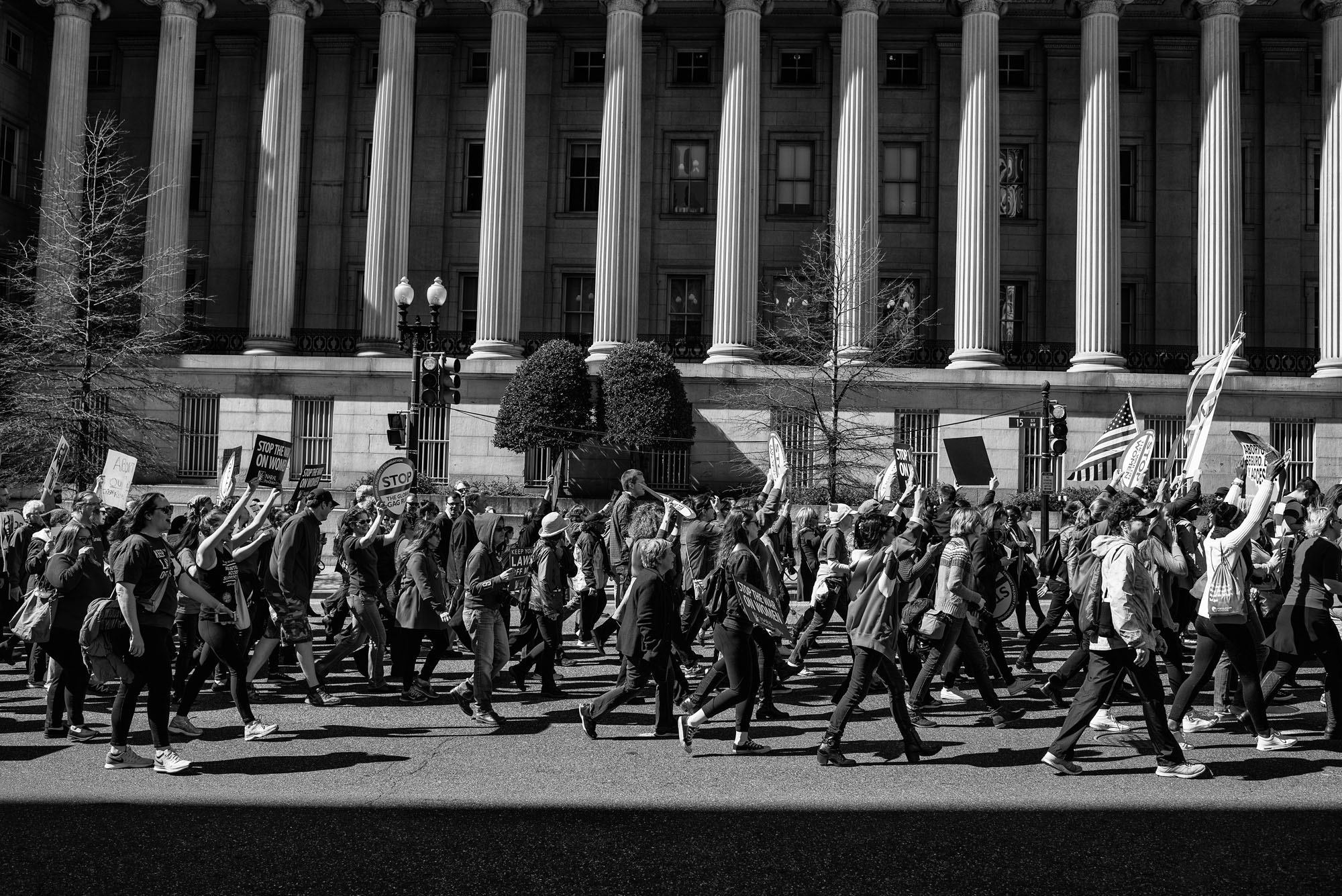 People march by the US Department of the Treasury at the Day Without Women protest in Washington, DC on March 8, 2017.