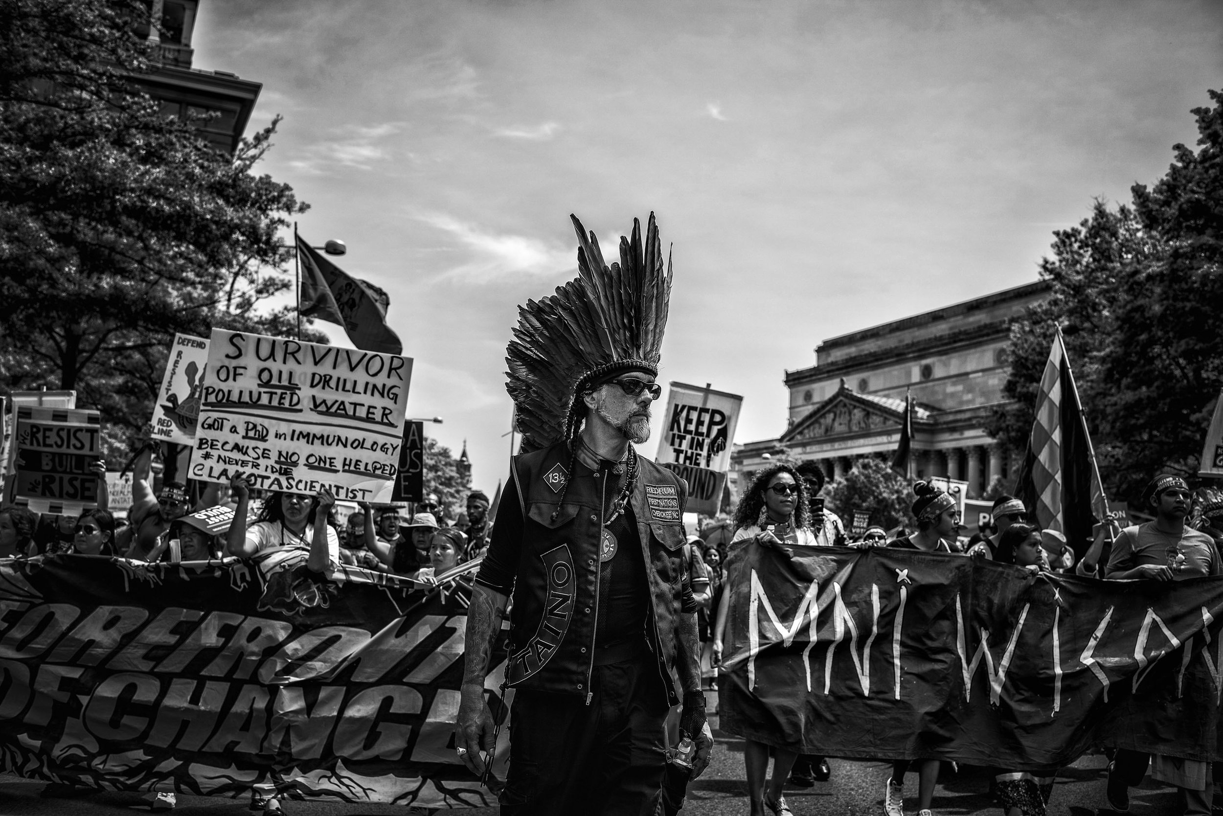 Day 100 : A member of the Redrum First Nations Motorcycle Club, a group of Native American bikers, sports a headdress while walking down Pennsylvania Avenue for the People's Climate March.