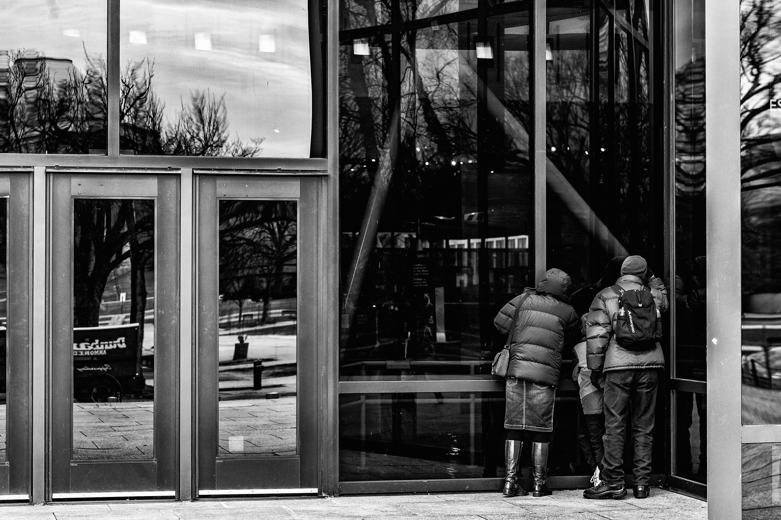 Day 718: Tourists from Australia look into the window of the National Air and Space Museum in Washington, DC, on January 7, 2019. The museum, along with all Smithsonian Museums is closed due to the government shutdown.