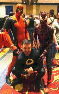 Author Pablo Greene may not be in rubber, but the hot rogues flanking him sure are