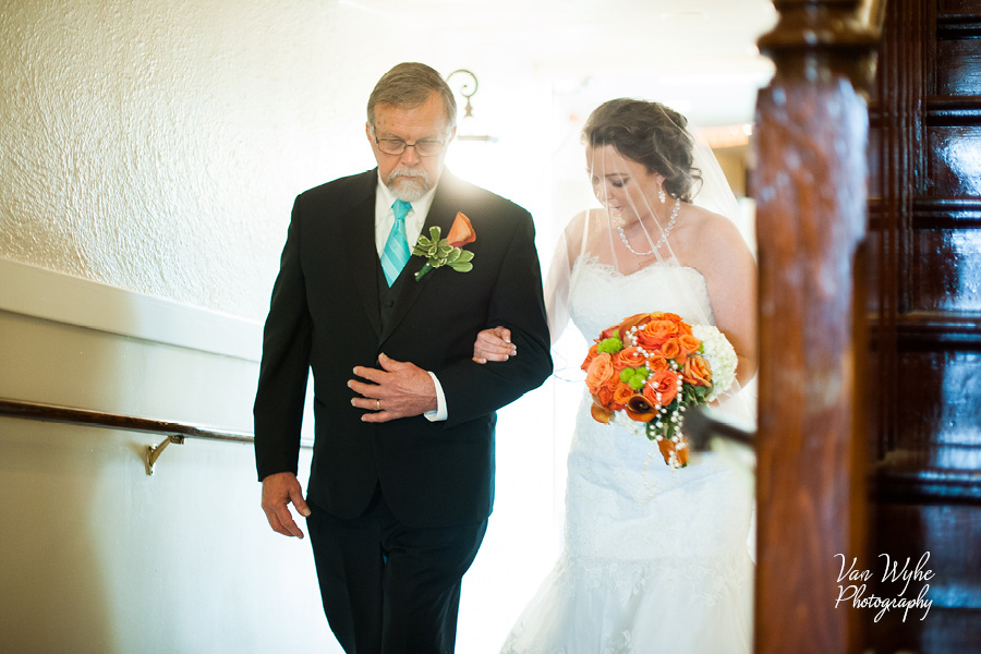 A bride and her father make their way towards the chapel.