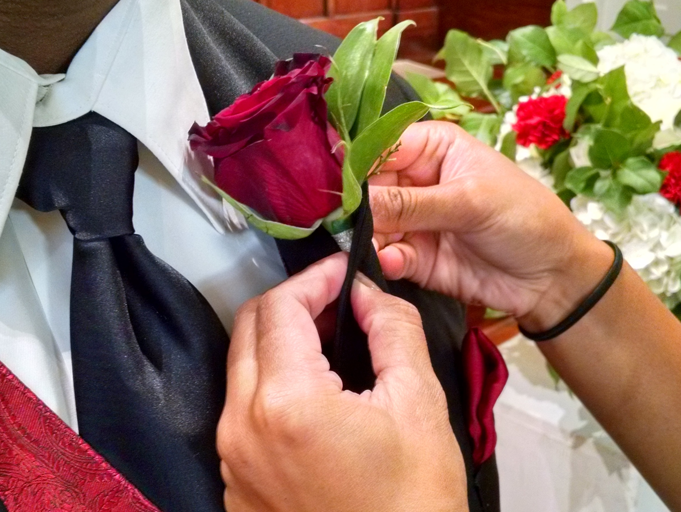 You're sort of wrapping the fabric of the lapel around the stem of the boutonniere to make it easy to pin through the layers.