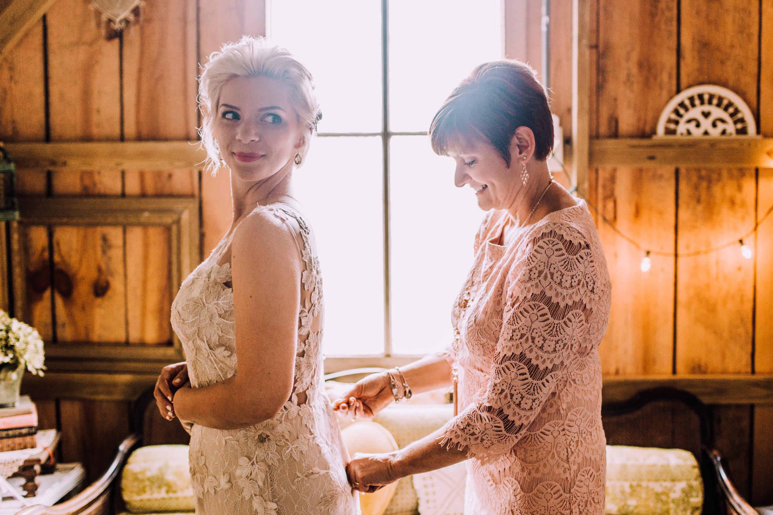 mom zips up daughter's wedding dress