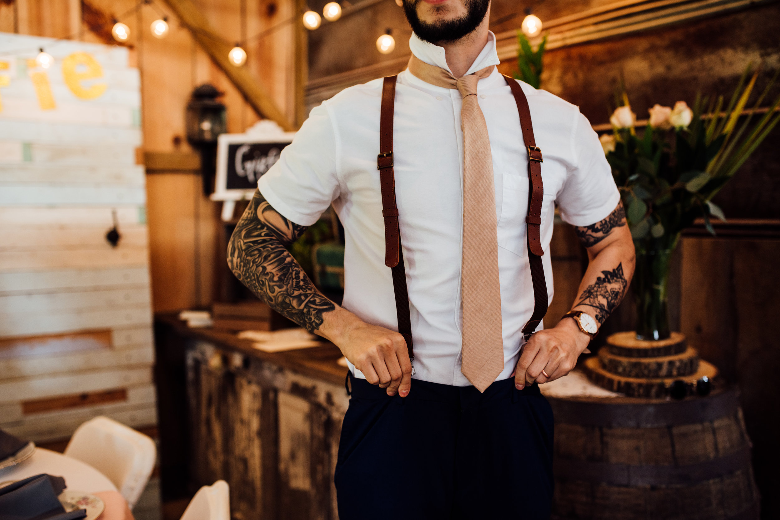 groom with tattoos and suspenders
