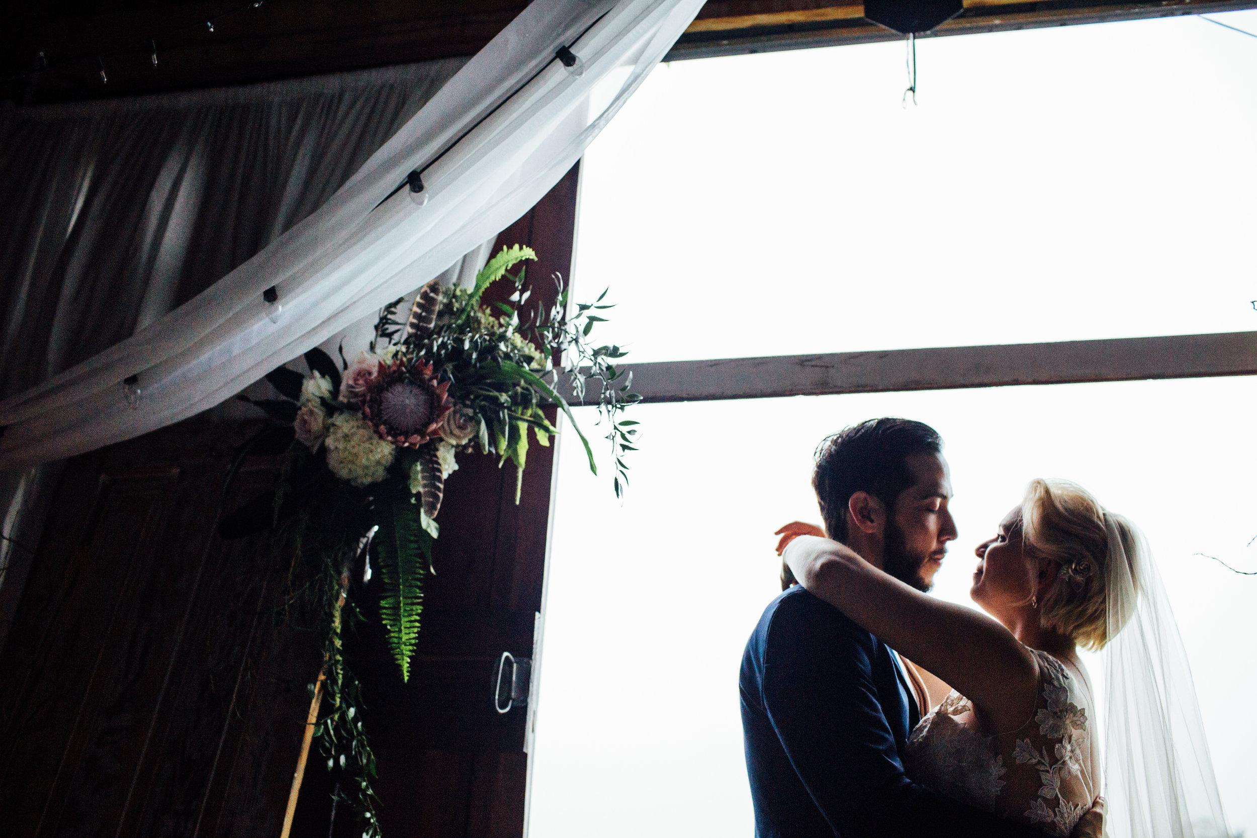 bride and groom silhouette inside barn
