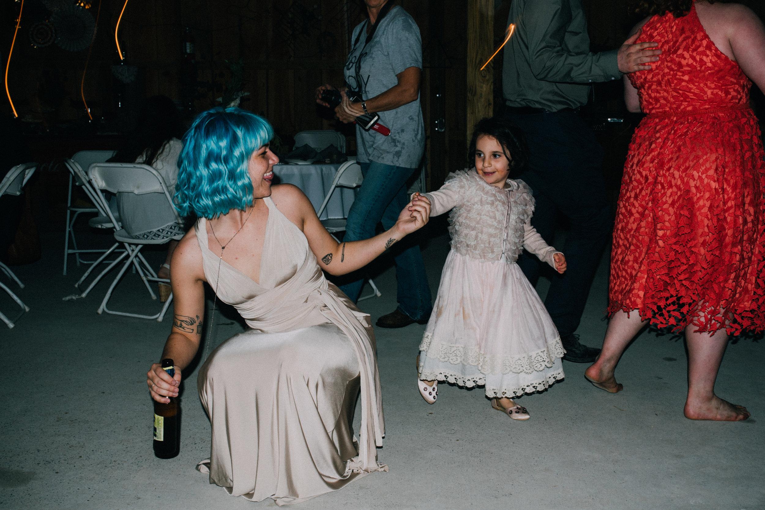 blue hair bridesmaid dancing with flower girl