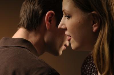 Woman whispering in her boyfriend's ear
