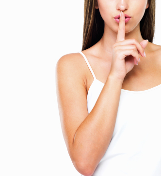 Woman with finger to lips indicating secrecy