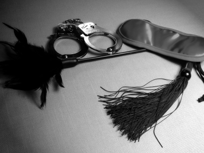A collection of BDSM sex toys, including handcuffs, a blindfold, and a whip