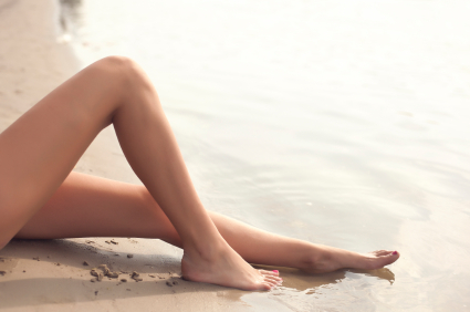 Close-up of a woman's bare legs on the beach