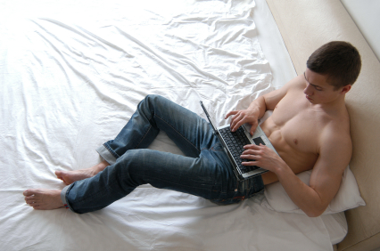 shirtless-man-using-laptop-in-bed.jpg