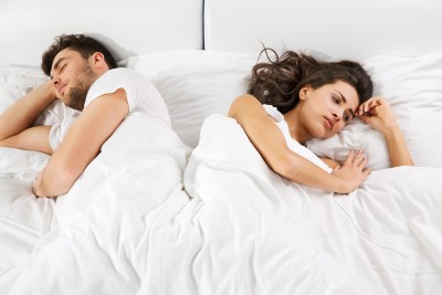 Man and woman in bed together and turned away from each other. Woman looks distressed