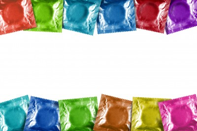 Two rows of condom packages lined up, each in a different color