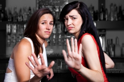 Two women in a bar rejecting a male suitor with bad behavior