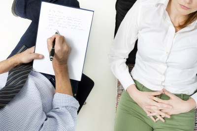 Sex therapist taking notes on patient who is sitting on a couch