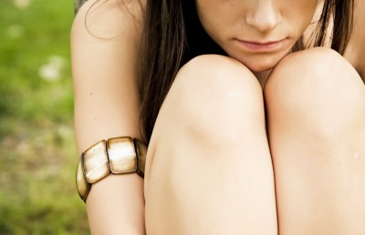 Depressed woman crouched with arms wrapped around her legs