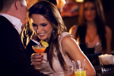 Man whispering something to a woman at the bar while she laughs