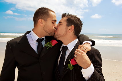Gay male couple kissing on the beach after getting married