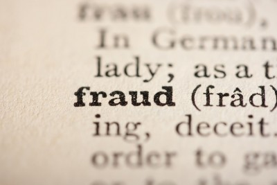 """Close-up of the word """"fraud"""" typed in an old dictionary"""