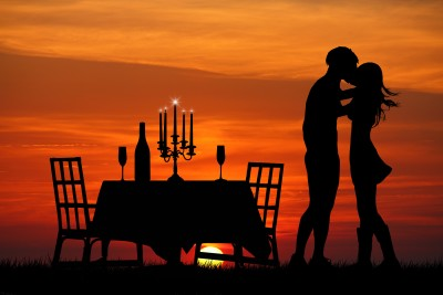 Couple kissing at sunset on the beach after having a romantic candlelight dinner