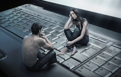 Conceptual photo of a couple sitting on a laptop keyboard to symbolize online dating