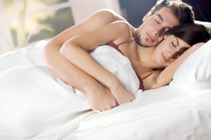 Couple sleeping with their arms wrapped around each other