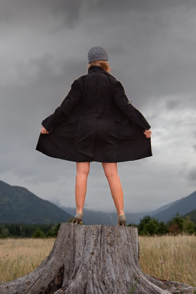 Woman in a trenchcoat standing on top of a tree stump and exposing herself to the world